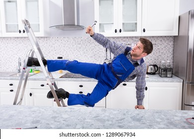 Young Male Carpenter Falling From Metal Ladder In Kitchen With Hand Tool