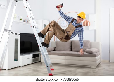 Young Male Carpenter Falling From Metal Step Ladder In Living Room