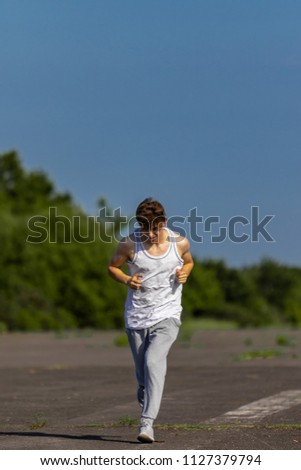 Young male caucasian adult jogging outside on a warm summer's day