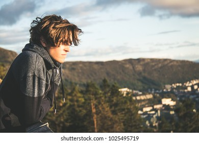 Young male caucasian male standing on a panoramic viewing point heading into the distance above the city of bergen in norway during sunset