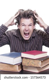 Young male Caucasian student reacts shockingly pulling out his hair with pile of academic books before him on white background
