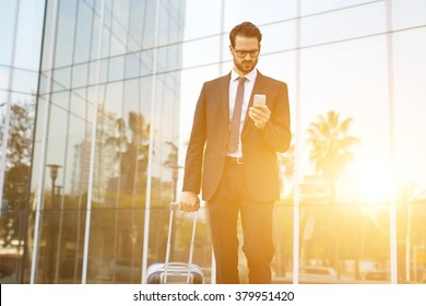 Young male CEO with suitcase reading text message on cell telephone while walking outdoors near building with city reflection, intelligent employer dials the number on smart phone before business trip