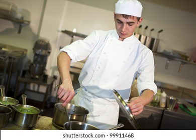 Young male chef cooking meal at the stove stirring food in a pan