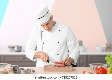 Young male chef cutting meat on wooden board in kitchen