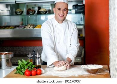Young male chef preparing pizza dough