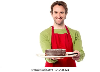 Young male chef presenting birthday cake