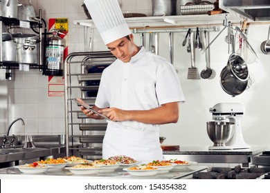 Young male chef using digital tablet with pasta dishes at kitchen counter