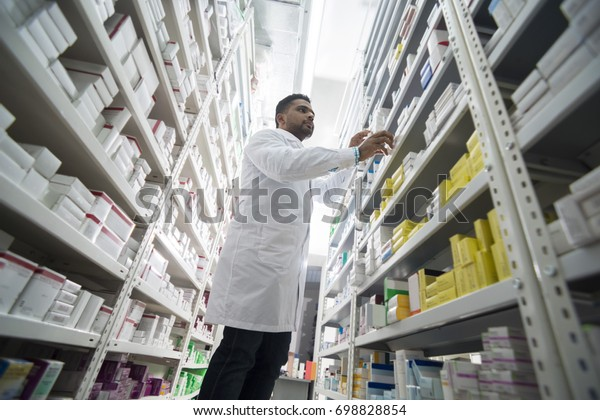 Young Male Chemist Arranging Products In Shelves At Pharmacy