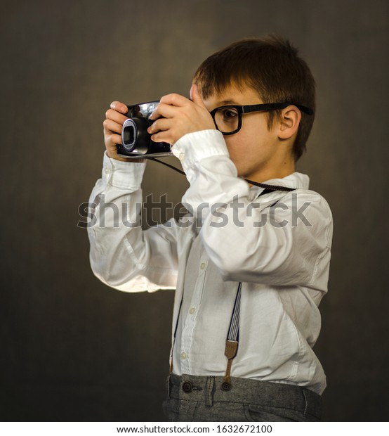 Young male child holding an antique, retro camera.