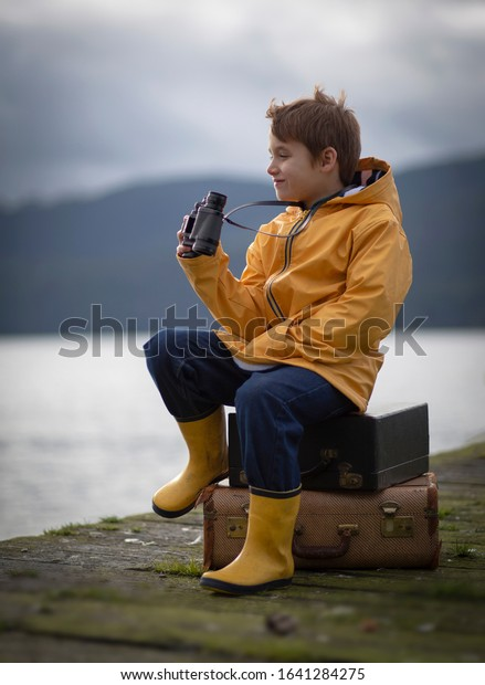 Young male child sitting on a wooden pier wearing a yellow rain jacket and boots holding binoculars.