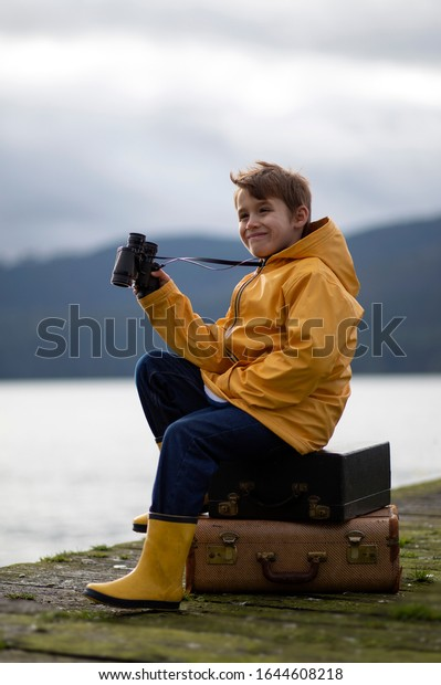 Young male child sitting on a wooden dock wearing a yellow rain jacket and holding black binoculars.