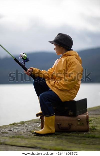 Young male child sitting on a wooden pier holding a fishing rod wearing a yellow rain jacket.