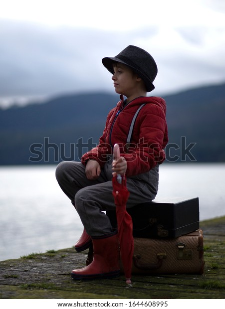 Young male child sitting on a wooden pier wearing a red jacket holding a red umbrella.