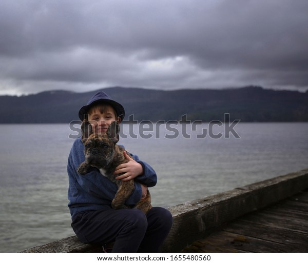 Young male child sitting on a dock holding his French Bulldog puppy with water in the background.