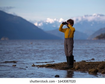 Young male child standing on a rocky beach looking through binoculars wearing large rubber boots.