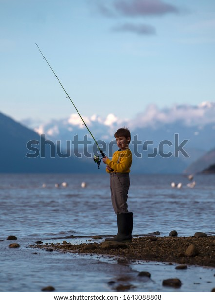 Young male child standing on a rocky shore holding a green fishing rod wearing large rubber boots.
