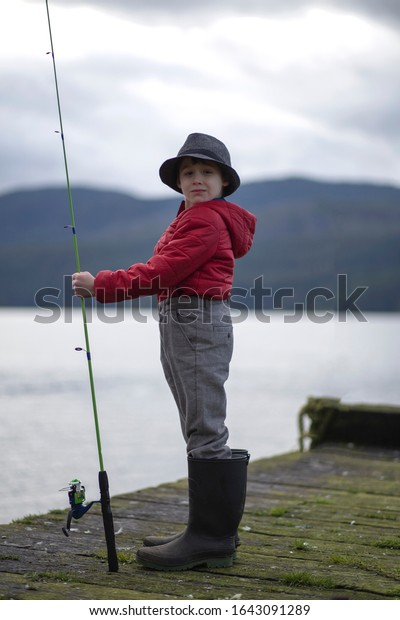 Young male child standing on an old wooden dock holding a fishing rod wearing large rubber boots.