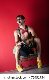 Young male circus performer seated backstage in front of red wall