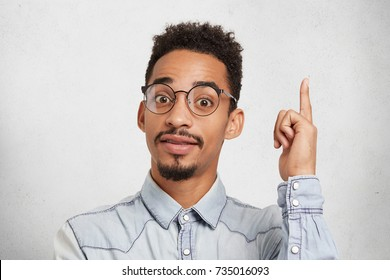 Young male clever student wears glasses and denim shirt, raises index finger as gets idea how to make interesting project together with groupmates. Creative man has something intriguing in mind