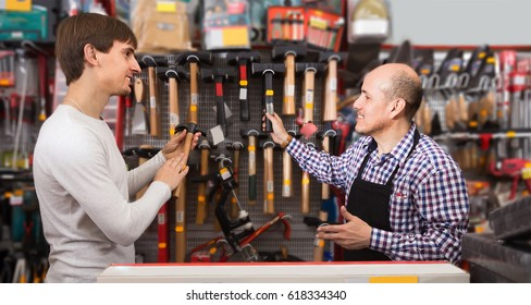 young male client and salesman with hammer at tooling section in building store