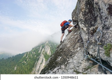 Young male climber climbing Via ferrata Astragalus, Romania, Europe in summer. Changing carabiners on cable.