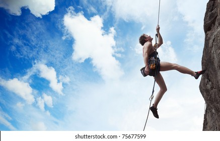 Young male climber hanging on a rope and looking to somewhere on blue cloudy sky background
