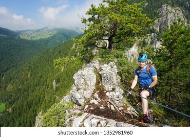 Young male climber on top of Via ferrata Astragalus, Romania, Europe in summer