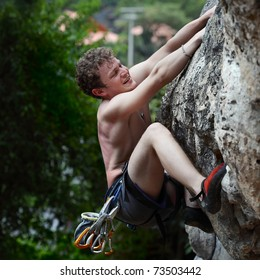 Young male climbing on a cliff on green trees background