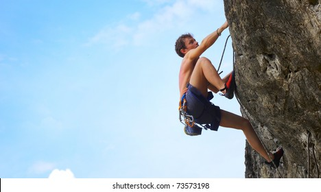 Young male climbing on a cliff on blue cloudy sky background
