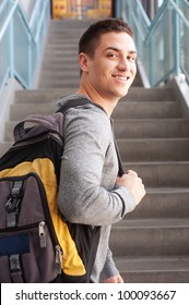 young male college student at school with backpack