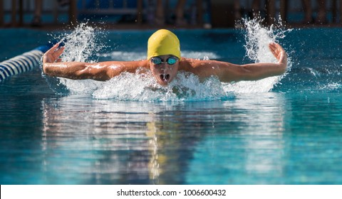 young male competes in swim competition in butterfly stroke with water splashes and  highlights in outdoor natural light