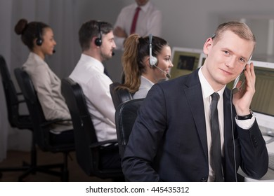 Young male consultant is talking on the phone and his collegues are supervised by manager