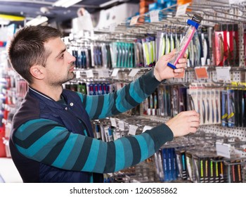 Young male consumer choosing ocean fishing lures in the fishing shop