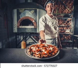 young male cook holding delicious appetizer on white plate