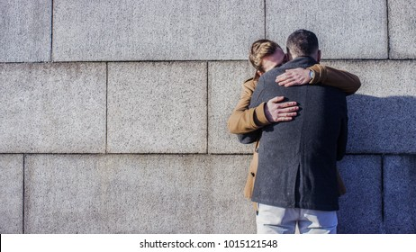 Young male couple embrace against a wall, with copy space