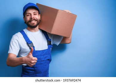 A young male courier in a blue uniform holds a parcel in his hands. Strong guy delivery man with a beard. The postman smiles on a blue background.