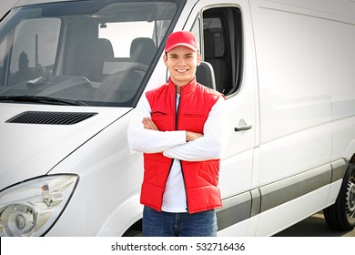 Young male courier near delivery service van