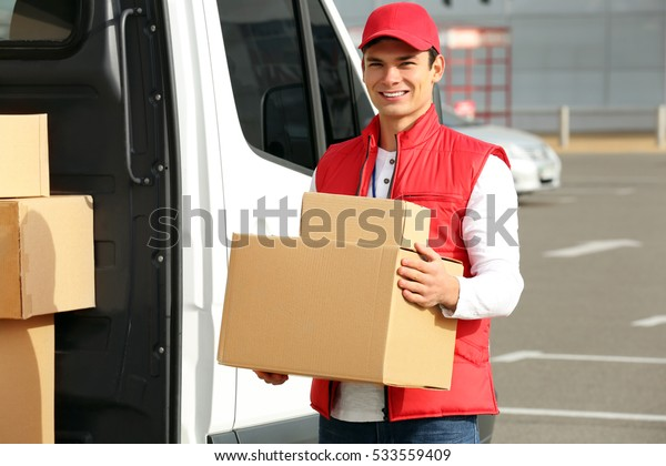 Young male courier with parcels near delivery service van