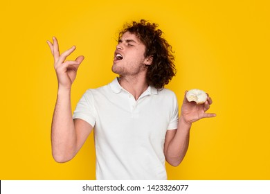 Young male with curly hair keeping eyes closed and gesturing with hand while tasting marvelous donut against vibrant yellow background