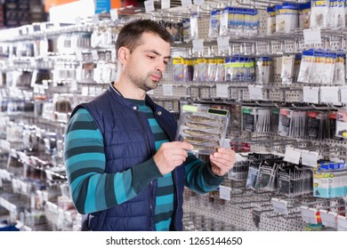 Young male customer choosing new fishing lures in the fishing shop