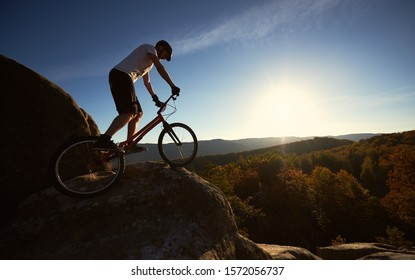 Young male cyclist balancing on trial bicycle, rider making acrobatic stunt on top of big boulder on summer sunny evening, blue sky and sunset on background.