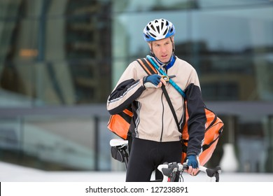 Young male cyclist with courier delivery bag using walkie-talkie