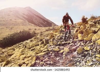 Young male cyclist going down a bike from a high mountain.