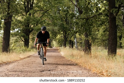 Young male cyclist in a helmet and glasses rides a bicycle on the countryside road. Athletic guy on a gravel bike enjoys training on fresh air.