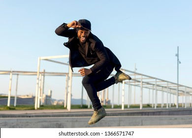 young male dancer in fashionable black clothes dancing blake dance on a street in the city on an autumn afternoon. Lifestyle.
