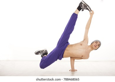 Young male dancer sitting on one hand, performing streetdance position , wearing ultraviolet pants. Horizontal image with copyspace, in studio, on white background and wood floor.