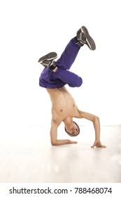 Young male dancer sitting on hands performing breakdance position upside down, wearing ultraviolet pants. Vertical image with copyspace, in studio, on white background and wood floor.