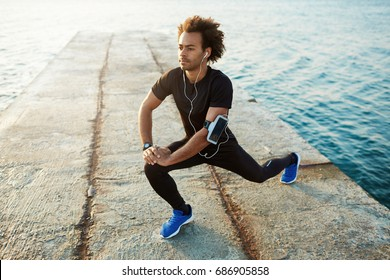 Young male dark-skinned runner with beautiful fit body warming-up his muscles before strength training cardio workout. Man athlete in sportswear stretching legs with lunge hamstring stretch exercise