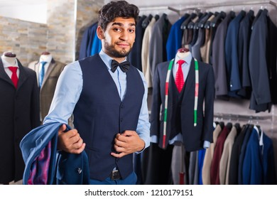 Young male is demonstrating image in waistcoat with butterfly in shop.