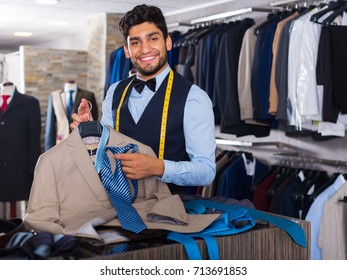 Young male designer is creating business image in men's clothes shop